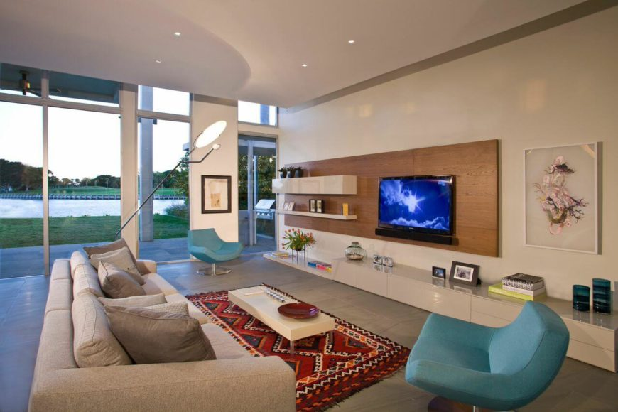 Immediately to the right of the foyer is the family room, with two modern light blue chairs and a series of floating shelves. The rear of the home is floor-to-ceiling windows that let in warm, natural sunlight.