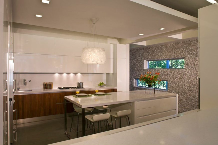 A view of the entire kitchen, showing the stone accent wall on the right and the contemporary light fixture with a subtle pattern above the island.