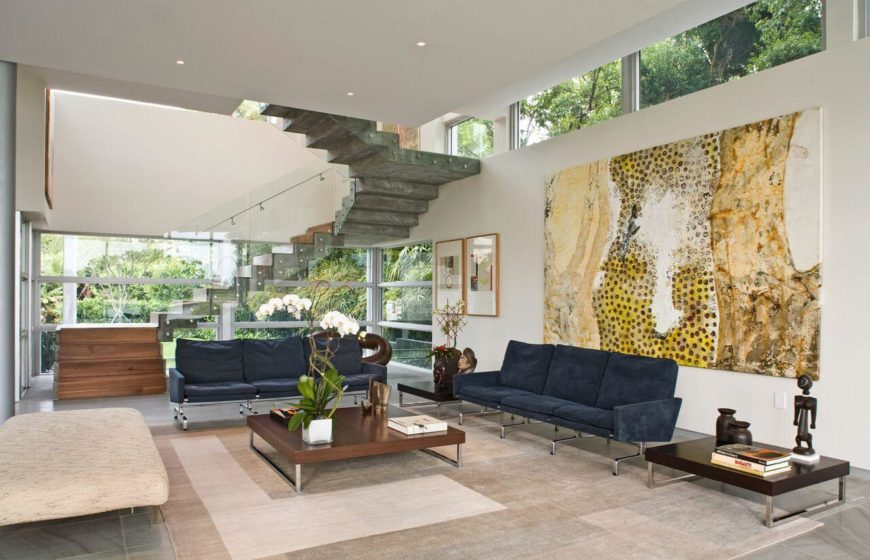 Beside the staircase is the navy and beige living room, with dark wood coffee tables and beautiful works of modern art, including sculptures.