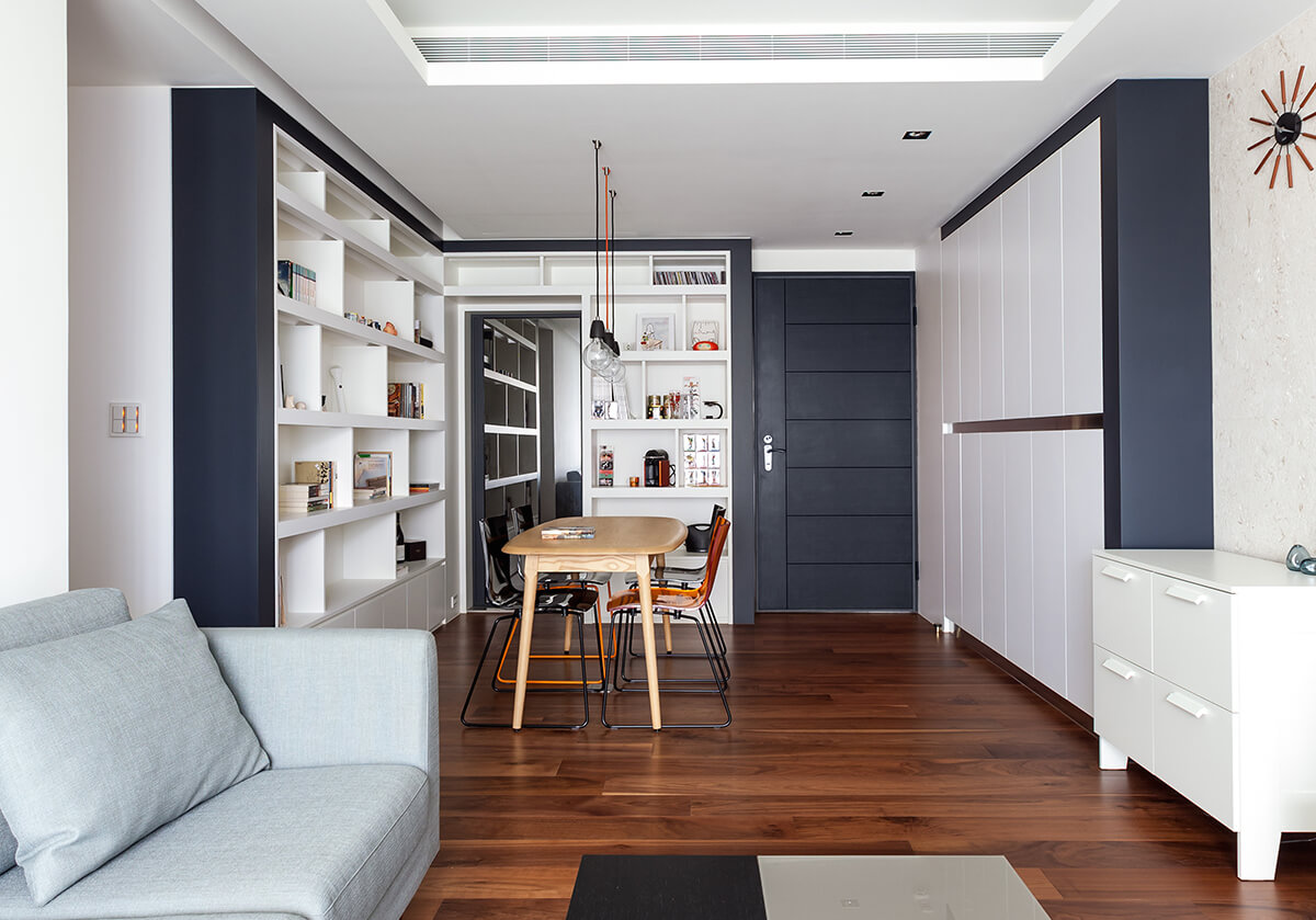 White and black dining space with hardwood flooring and built-in cabinet and shelves. It is lighted with small pendants that hung from the white ceiling.