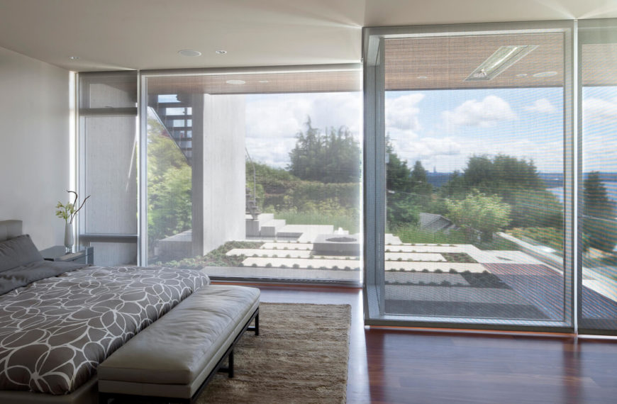 The primary bedroom, standing over a spread of rich hardwood flooring, enjoys the same spectacular views through full height wraparound glass. Subtle shades are drown for privacy and shade.