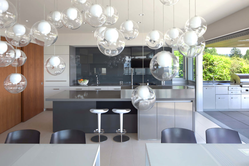 Across the divided dining table, we see the kitchen, highlighted by a large island in sleek brushed metal. A cloud of glass pendant lights hangs in the foreground, reflected in the glossy backsplash.