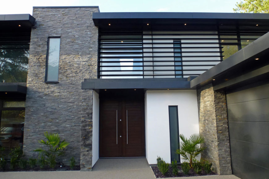 The front entrance is set back into the home, with rich dark wood doors and sleek metal hardware. The textural brick exterior complements splashes of white and black metal.