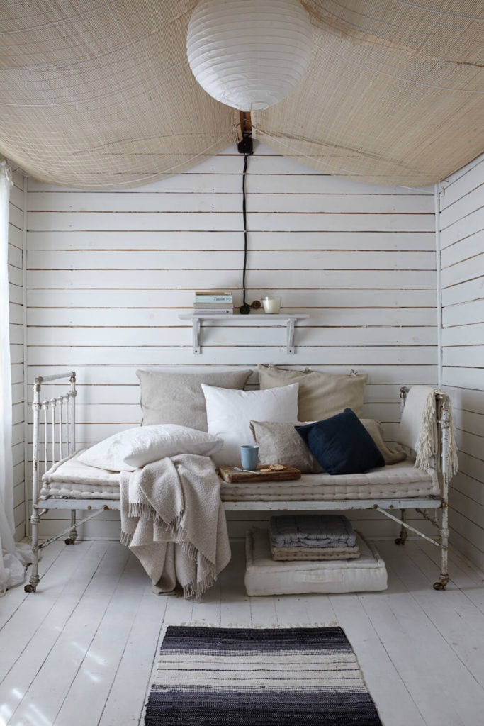 This secondary bedroom exemplifies the rustic style of the home, with an ancient metal frame bed standing over white painted flooring.