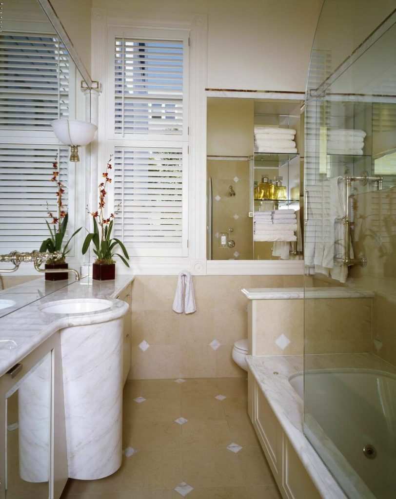 One of the home's bathrooms is in marble and beige tile. The sink bows out all the way to the floor. A small wall separates the shower area from the commode.