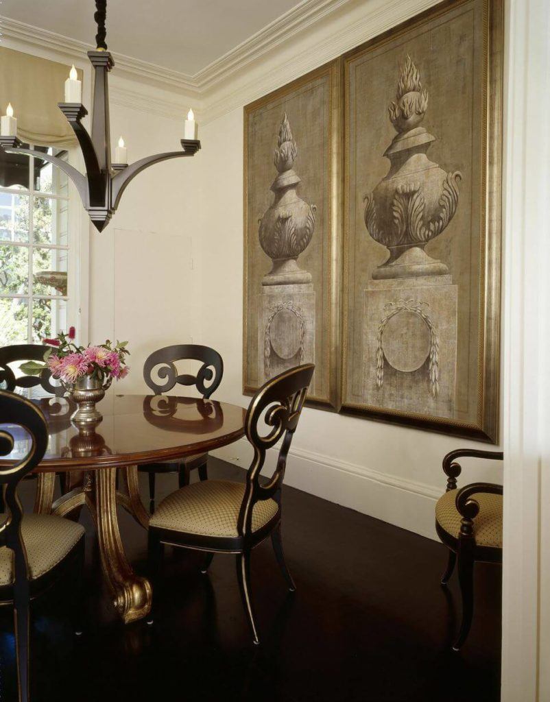 The stately dining room has a circular wooden dining table and ornate dining chairs. Enormous paintings on the right wall are fantastic accents to the already beautiful room. The dining room has a view of the garden.