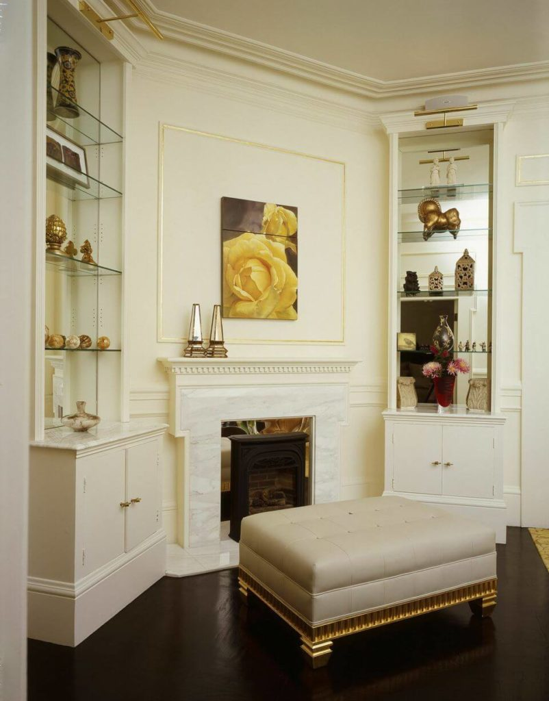 The white marble fireplace of the study is flanked by two small built-in cabinets topped by mirrors. A large white leather ottoman with golden supports contrasts with the luxurious dark wood floors.