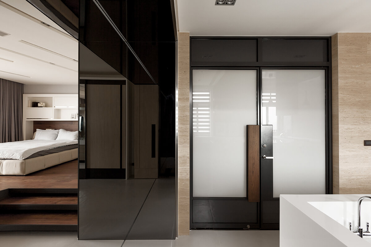 Returning to the main floor, next to the kitchen we see the bedroom, decked out in rich hardwood flooring on a raised platform. The front door features a mixture of metal, wood, and smoked glass.