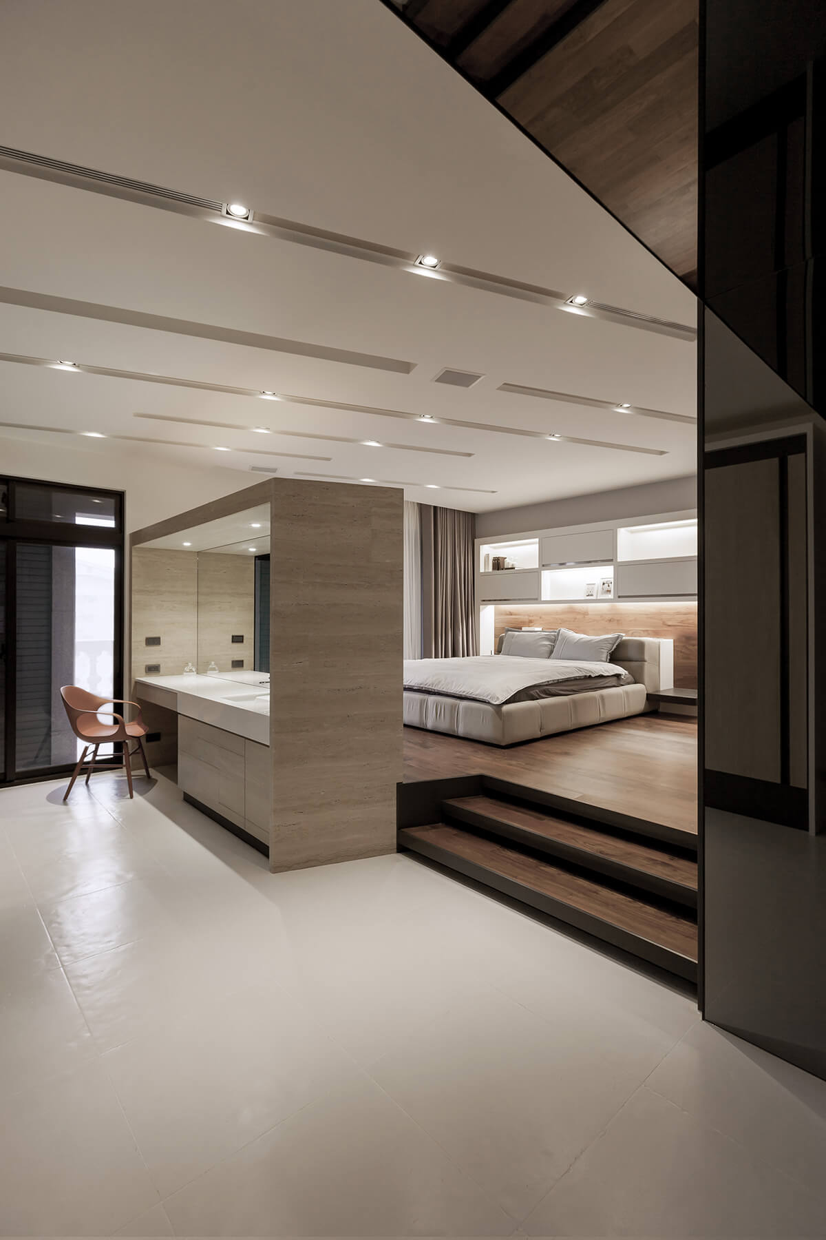 The bedroom en suite includes the marble wrapped vanity at left, helping bookend the bedroom itself. The raised hardwood flooring defines the comfy space.