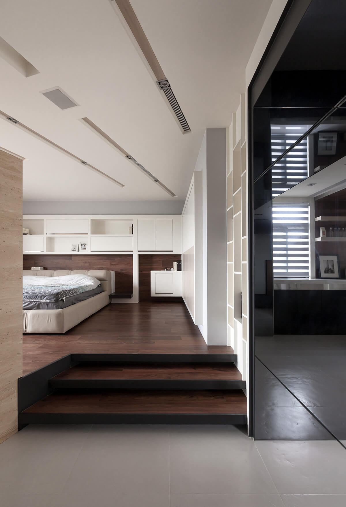 The mixture of rich natural wood tones and sleek white shelving in the bedroom makes for a striking high contrast appearance.