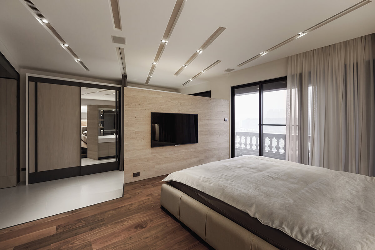 The bedroom features large sliding glass doors for private balcony access.