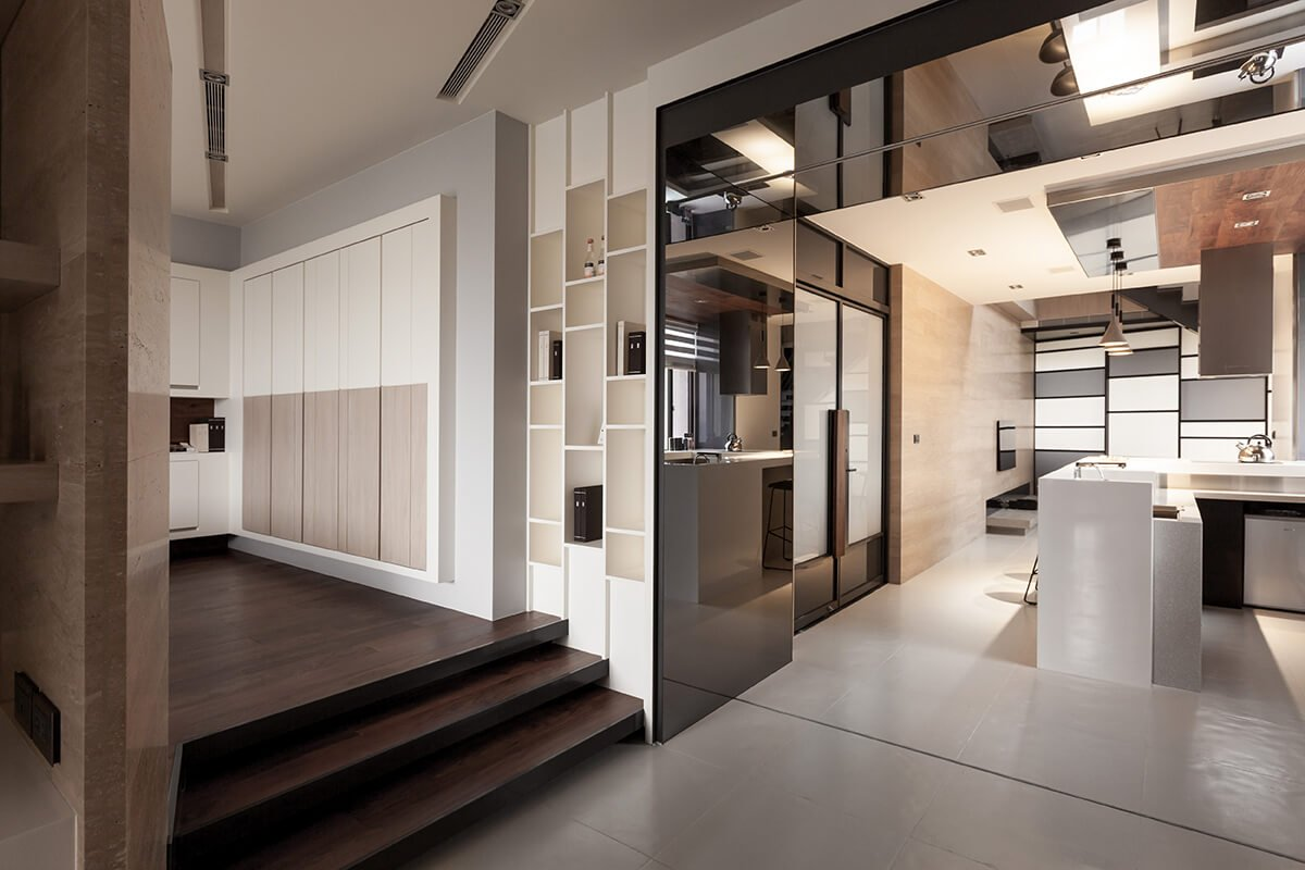 The intricate, interlocking open-plan design allows the flooring and other textural materials to distinguish different spaces within the home. Here we see the kitchen at right and private bedroom spaces to the left.