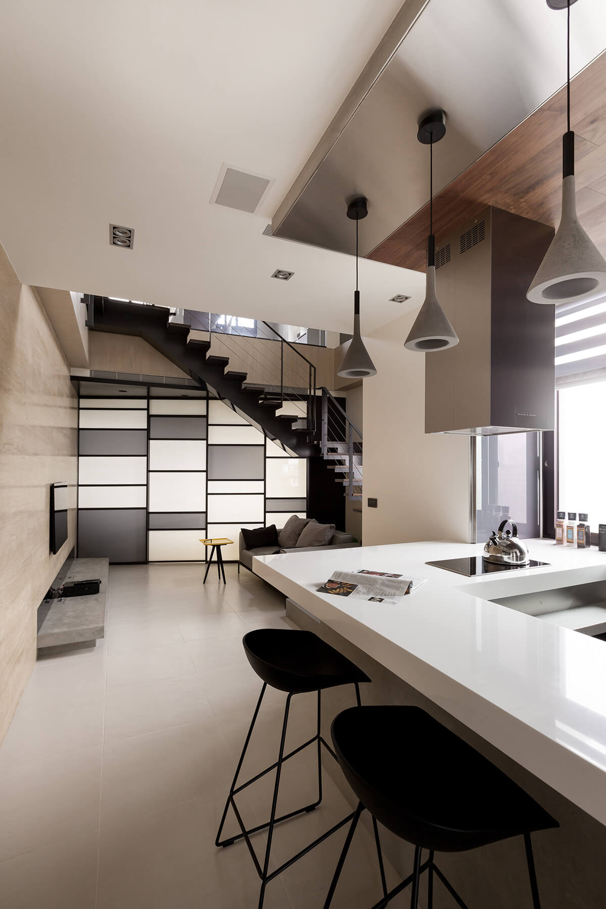 Pendant lights hang above the dining-space countertop at right, while we see a cozy living room space in the distance, standing beneath a checkered panel wall and set of open-design stairs.