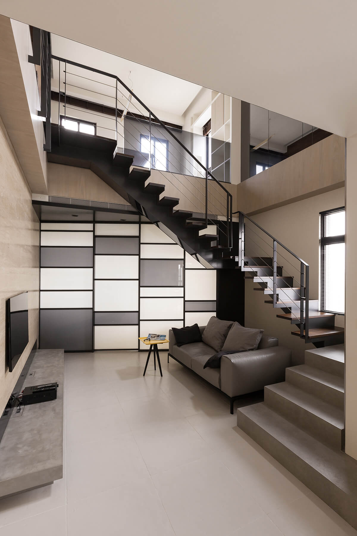 The central living room features a single leather wrapped contemporary sofa and tripod table, tucked beneath a metal and hardwood open-design staircase.