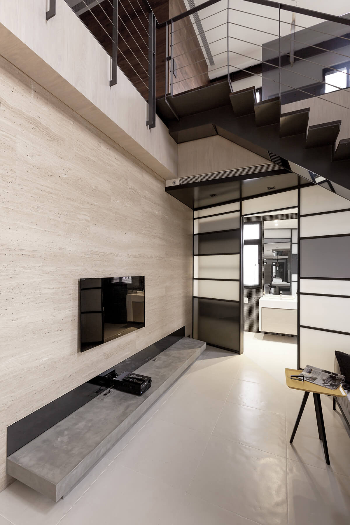 The black and white patterned wall in the living room slides open to reveal a bathroom, tucked beneath the staircase.