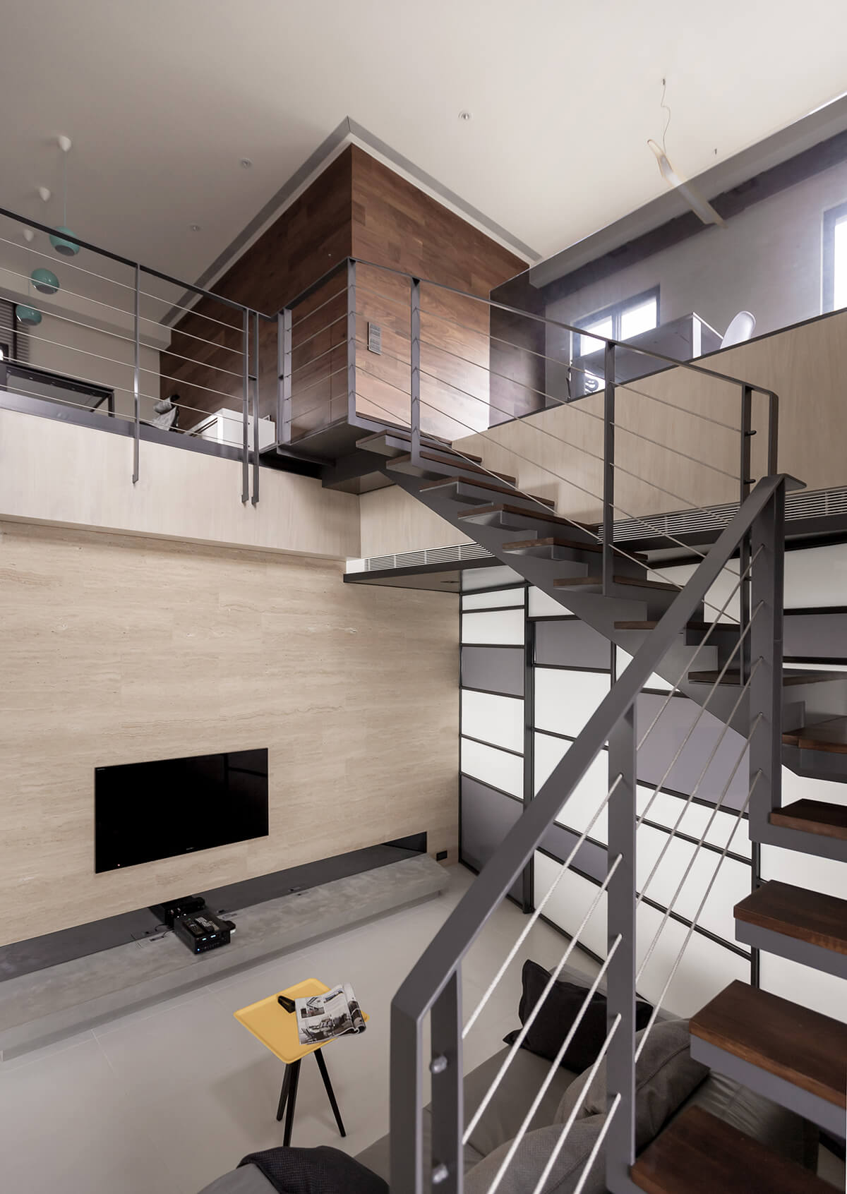 The central, high-ceiling part of the home features an expansive vertical layering of materials, with stone, marble, wood, and metal combining for a shifting, detailed visual presence.