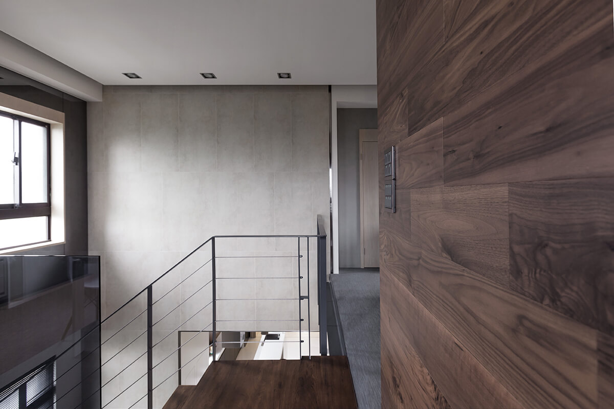 The upper level boasts rich, dark hardwood paneling as a defining feature. The low glass and metal railing provides safety and views toward the lower level.