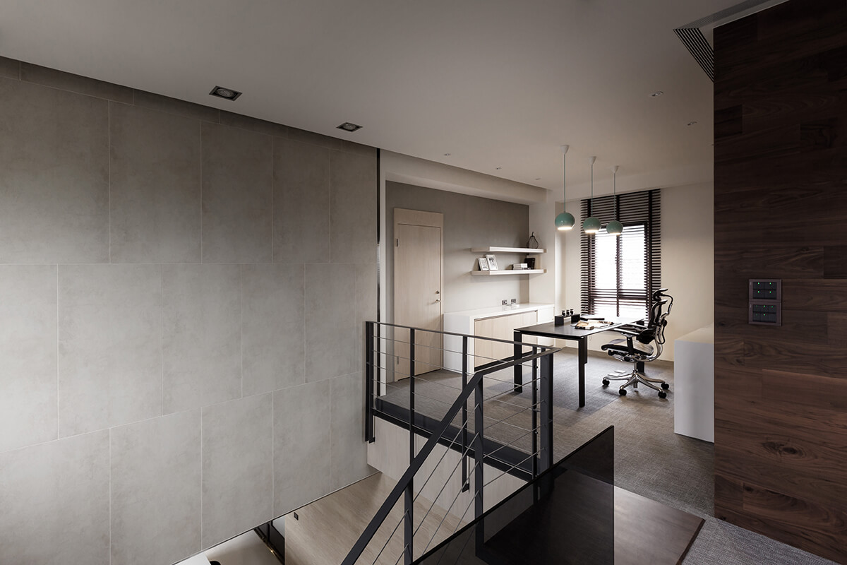 At the top of the stairs, we see this sleek home office space, centered on a large black desk.