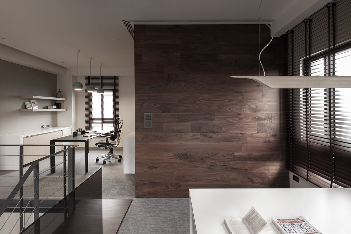 The other half of this open design space is another office area, with sleek white desk beneath a modern lighting rack. A trio of pendant lights hangs over the black desk at left.