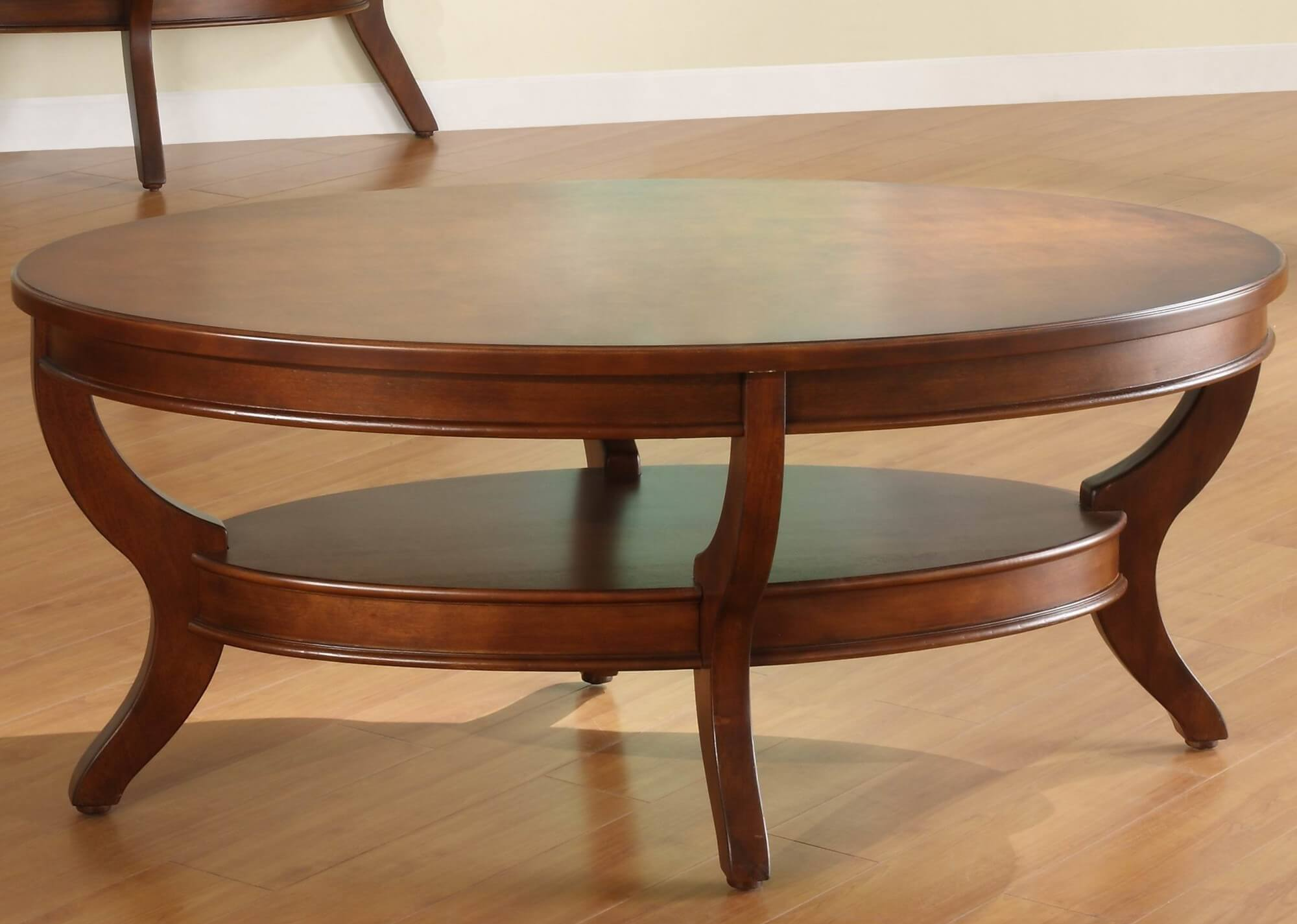 This intricately carved oval coffee table features two thick-slab surfaces, with a smaller lower tier for storage pinched between curved legs. Rich, warm toned stain helps it mix with almost any style room.