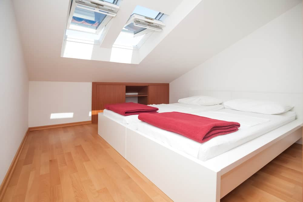 Modern style guest bedroom in attic with all white bed, white walls, white ceiling and skylights.