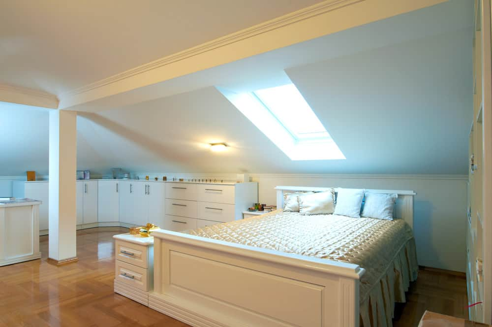 Gorgeous bedroom in attic with sleigh bed, skylight and built in cabinetry.