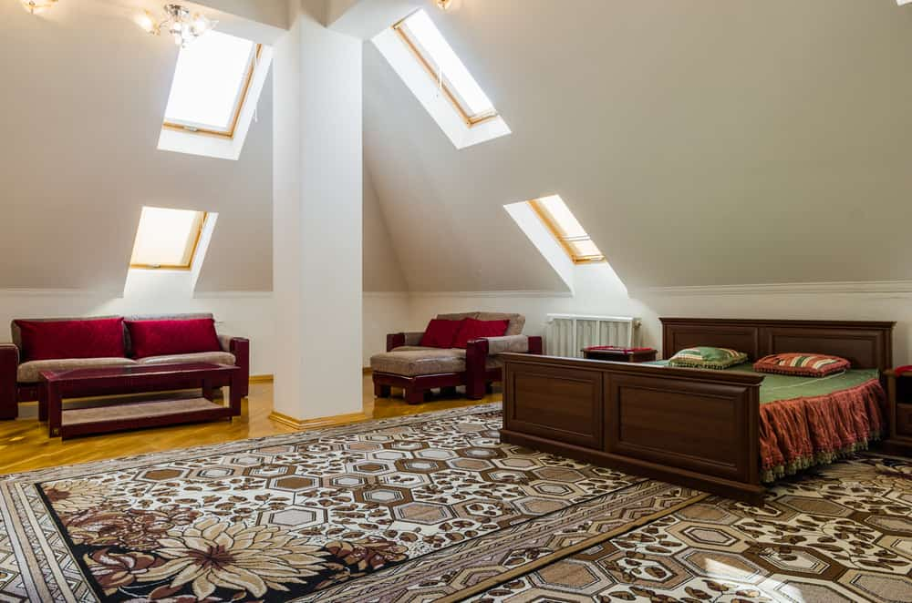 Master bedroom in attic with towering angled walls creating cathedral ceiling effect.