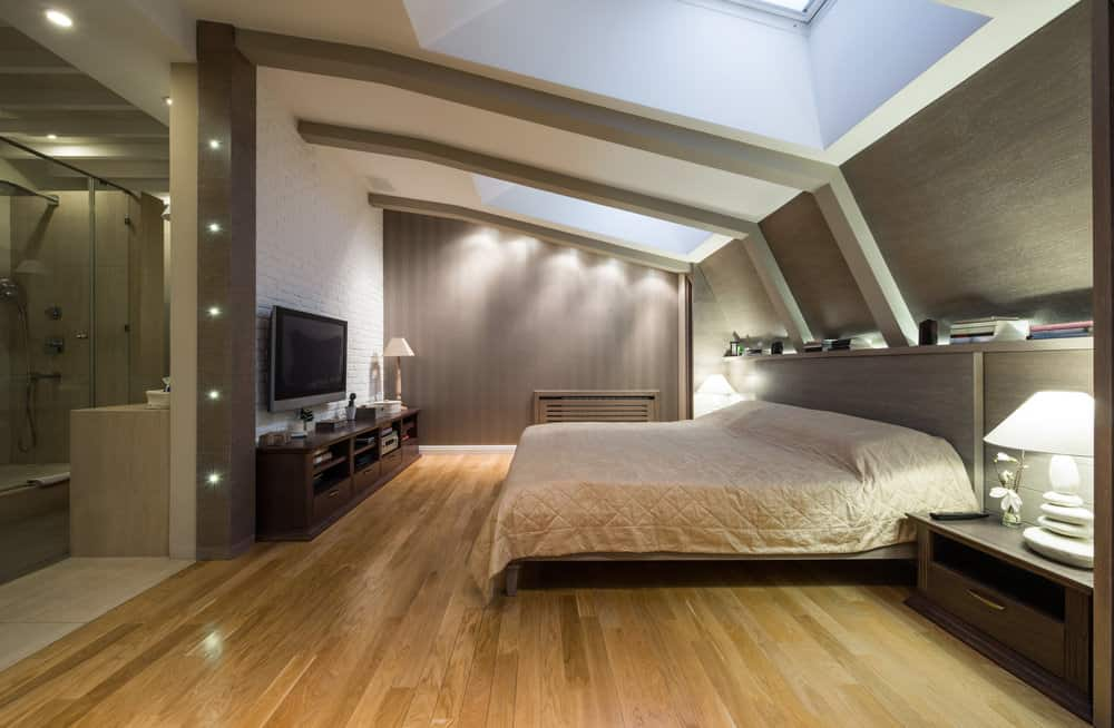 Sensational renovated loft master bedroom with dark green walls, skylights and light wood flooring.