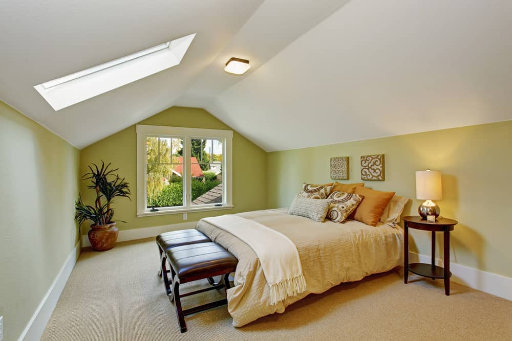 Large guest bedroom in attic with green walls, white ceiling and skylight.