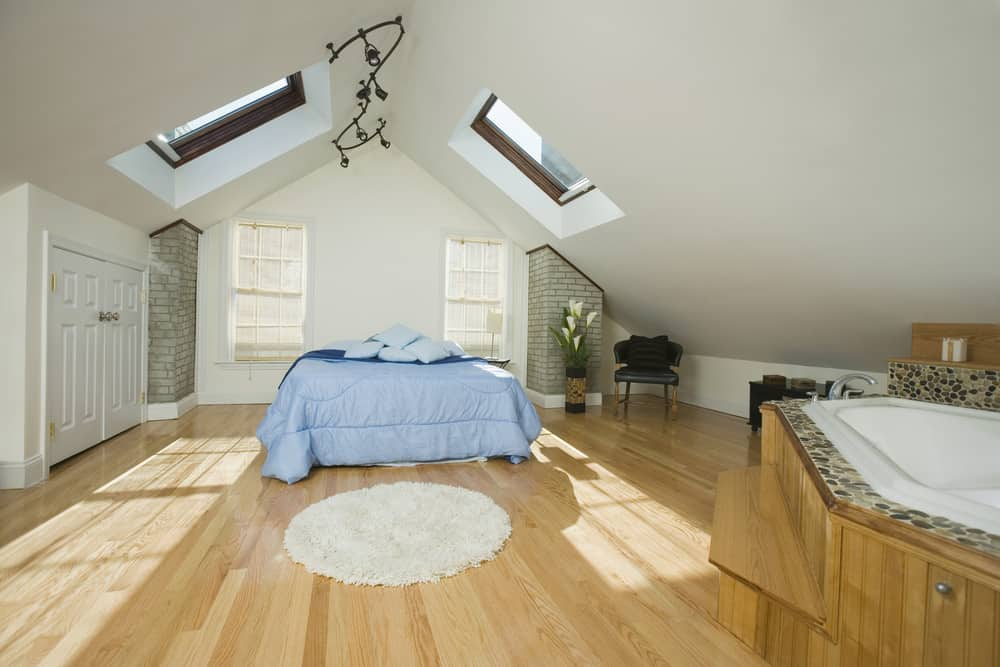 Huge guest bedroom with skylights, light wood flooring and open concept bathroom.