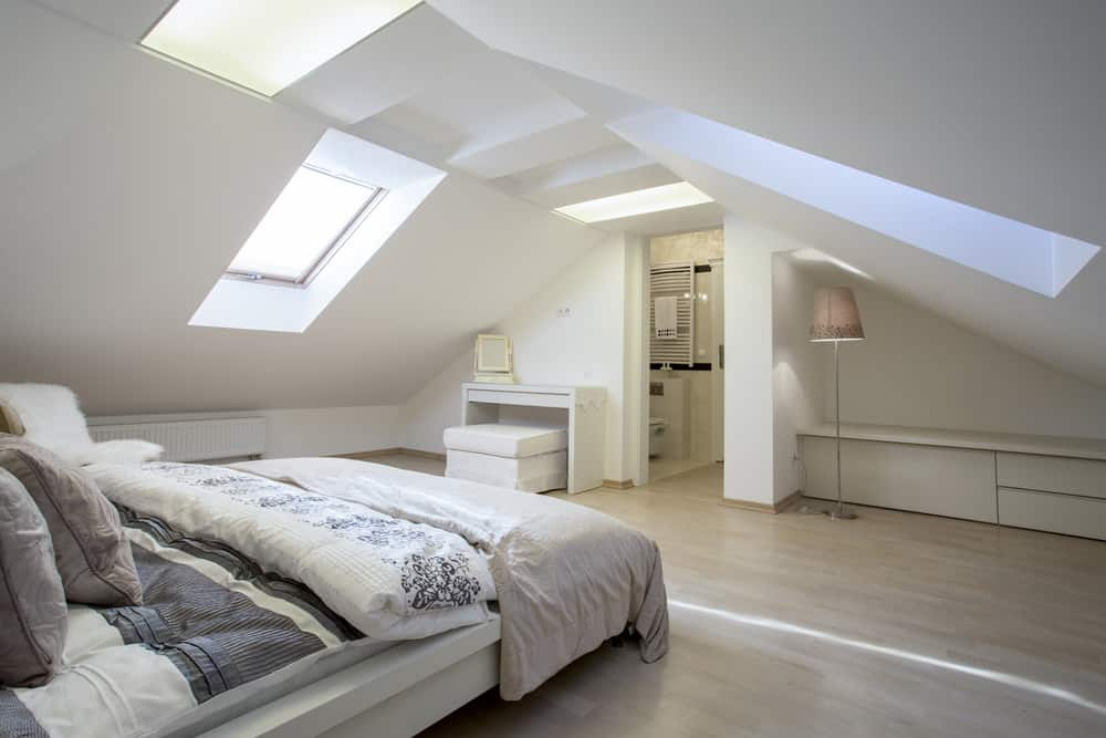 Large minimalist loft bedroom with skylights and white walls.