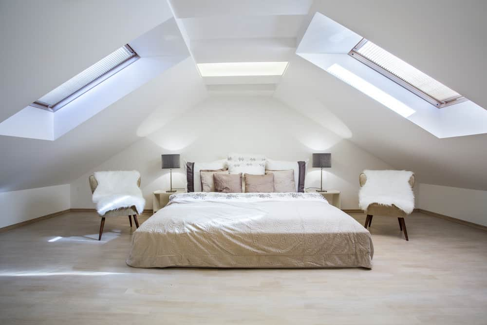 Gorgeous attic renovated master bedroom with white walls and ceiling. Bed flanked by stylish Mid Century modern chairs.