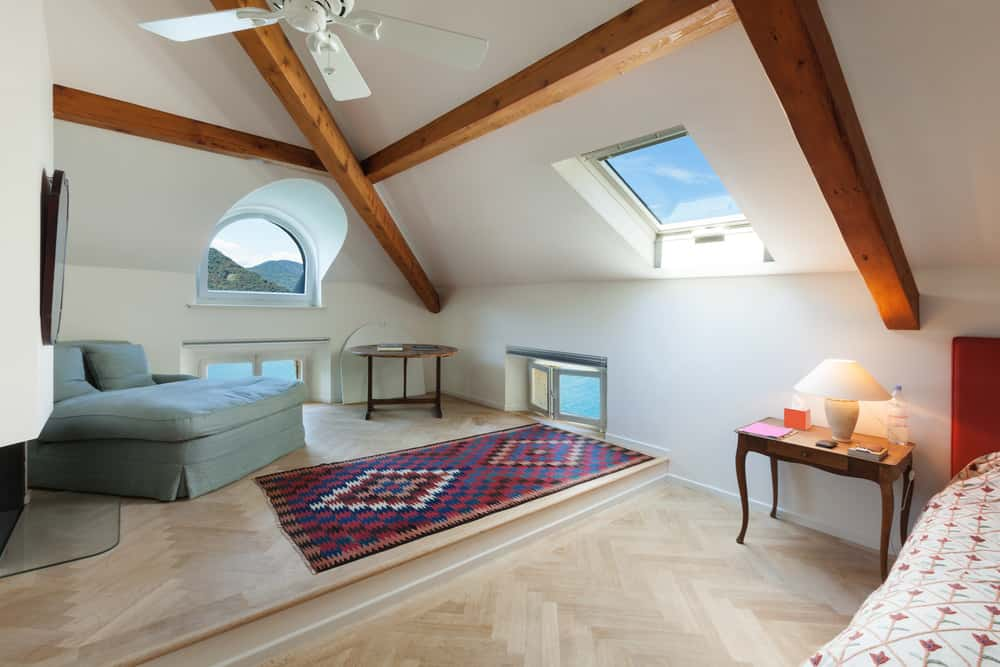 Spacious Scandinavian style attic bedroom with sitting area, wood ceiling beams and several windows.