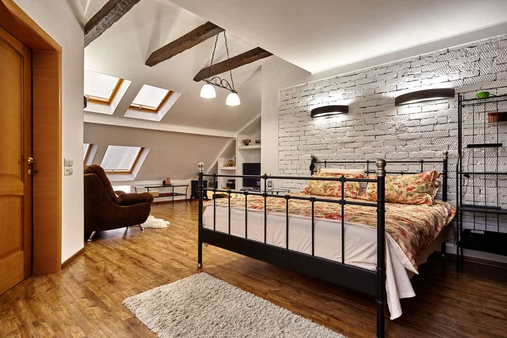 Spacious loft bedroom with wood ceiling beams and brick wall.