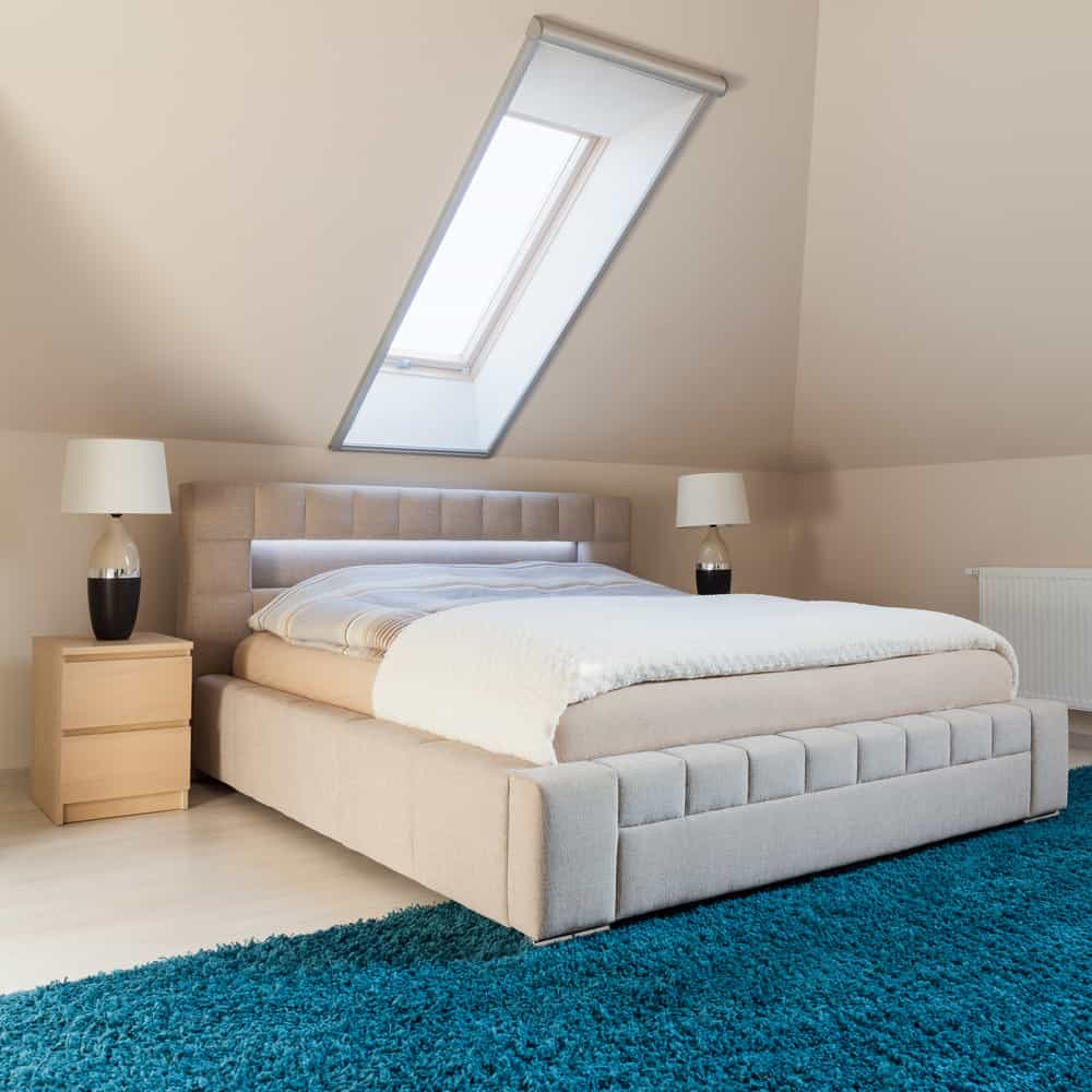 Stylish loft bedroom with blue are rug and large new bed under skylight.