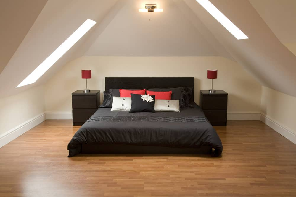 Sparsely furnished, minimalist loft bedroom with two skylights, wood flooring and black bedroom furniture (black bed, bedding and nightstands).