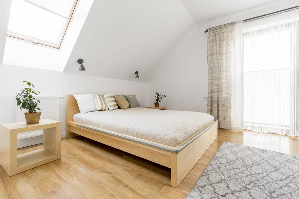 Sparsely furnished bedroom in attic with platform bed.