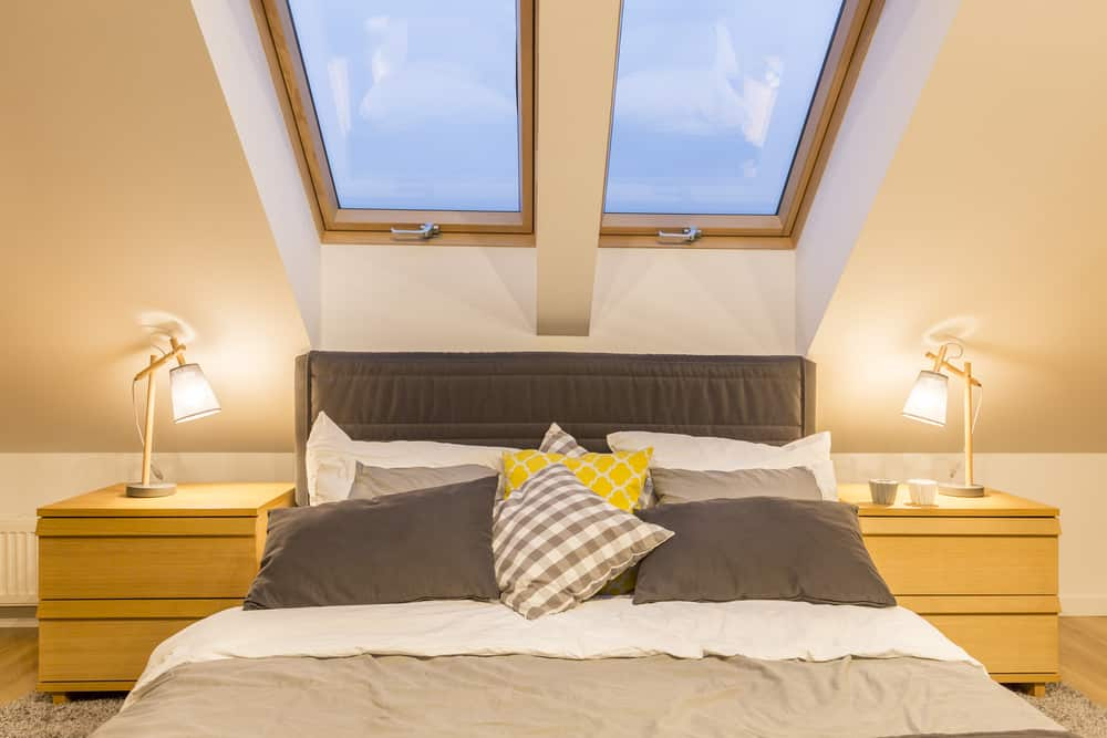Close up of bed in master bedroom under 2 skylights.