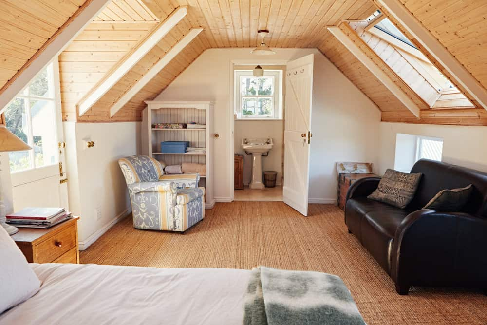 Large attic bedroom with wood ceiling, en suite and sitting area.