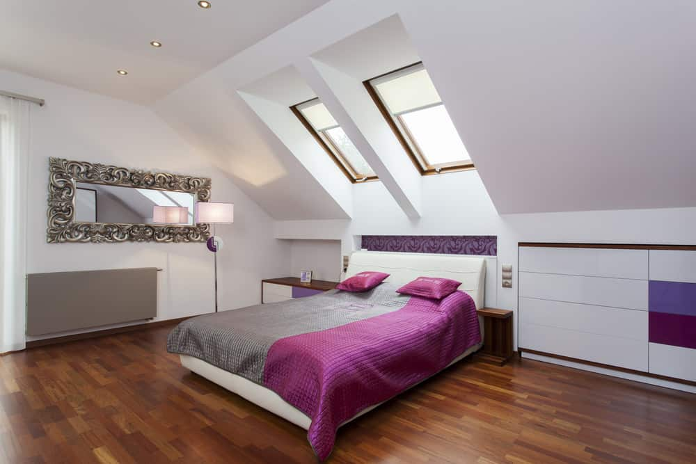 Stylish teenager bedroom in attic with skylights and hardwood flooring with purple and gray bedding.