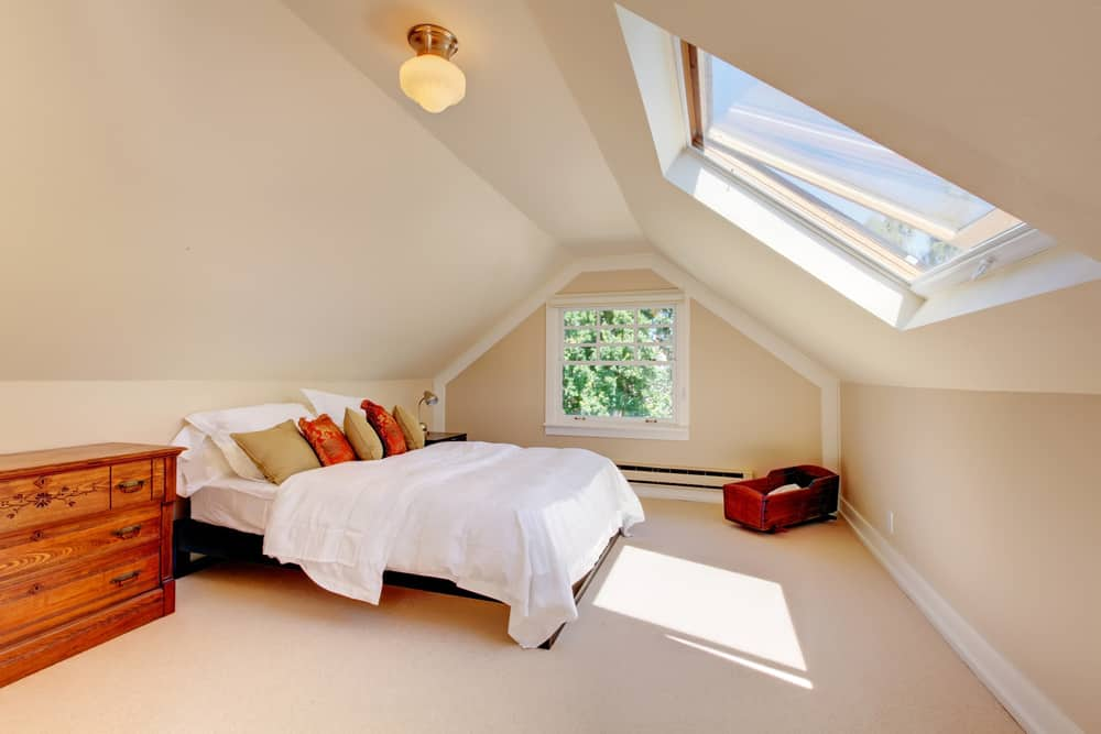 Simple attic guest bedroom above the garage with dresser and skylight