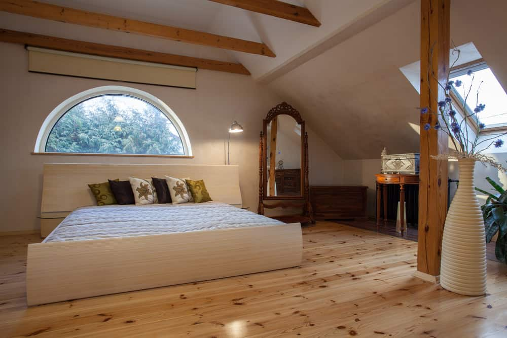 Southwestern style loft bedroom in attic with exposed ceiling beams, arched window and amazing wood flooring.