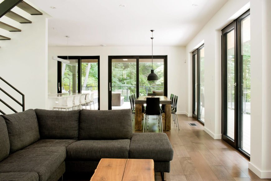 The central open-plan space includes living room, dining, and kitchen functions, all naturally lit via wraparound glazing and sliding glass doors.