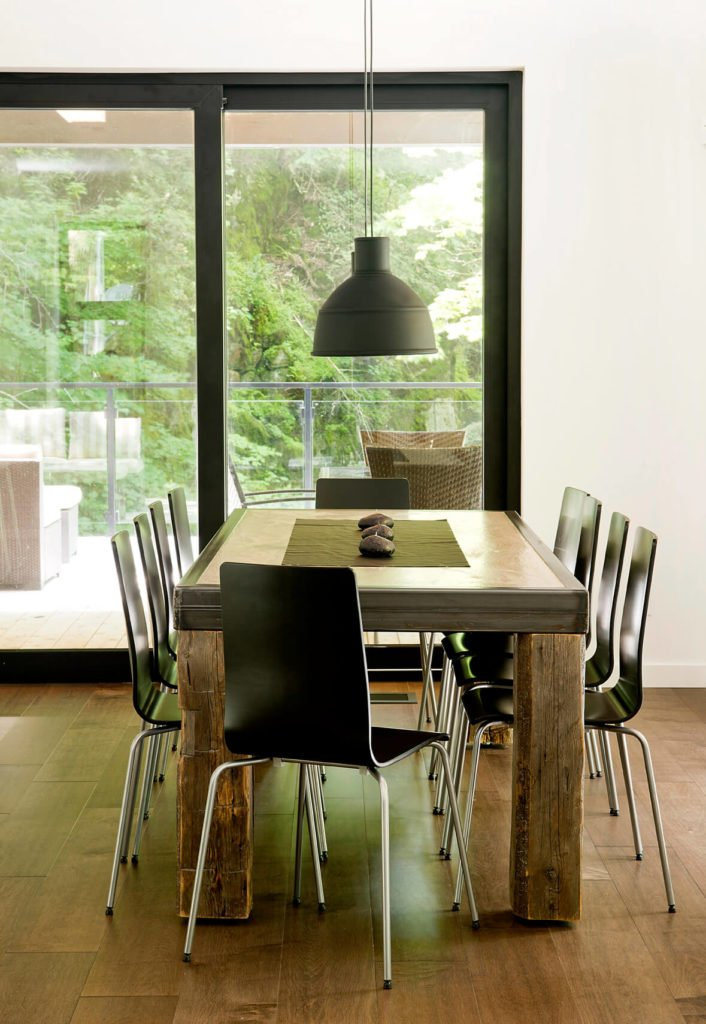 The massive dining table is a unique modern rustic creation, with worn beam legs supporting a metal rimmed tabletop below large pendant lights.