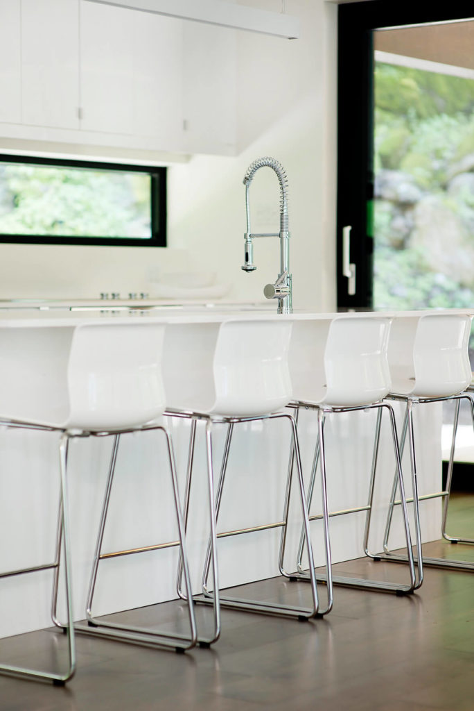 The kitchen countertop includes a lengthy dining area with attendant metal and acrylic bar stools.