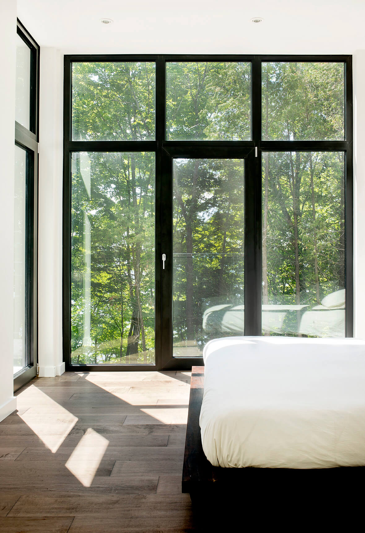 On the top floor, the primary bedroom enjoys expansive views of the surrounding forest and lake beyond.