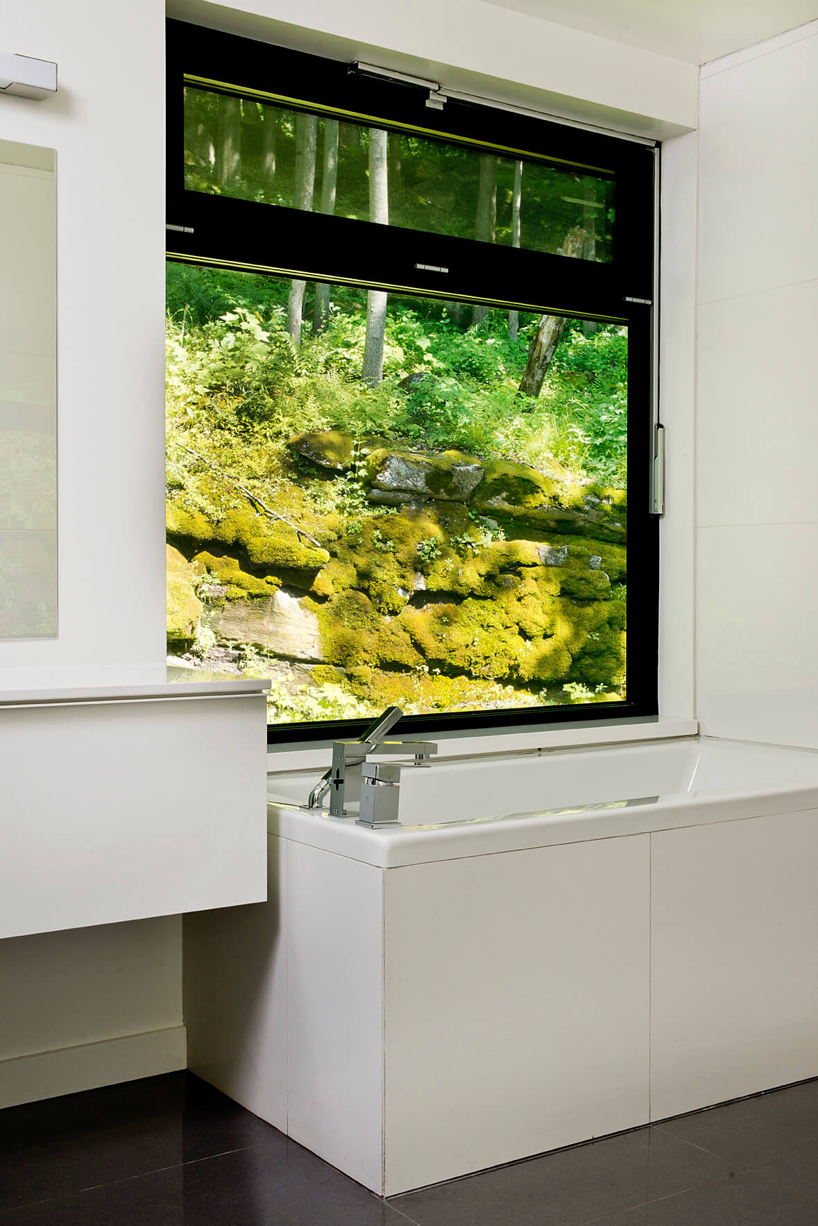 Lower level bathroom features hillside views from the soaking tub. Large format dark tile flooring contrasts with pristine white countertops and walls.