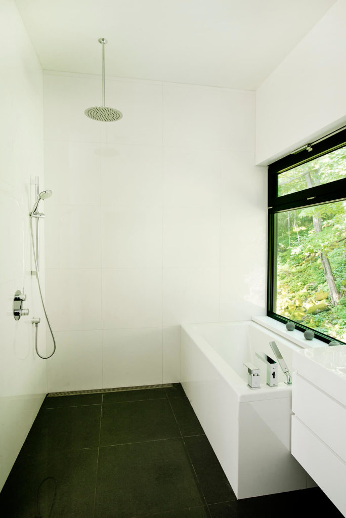 The upper level bathroom features a unique fully-open shower design, incorporating a drain on the edge, allowing the entire space to be washed down.
