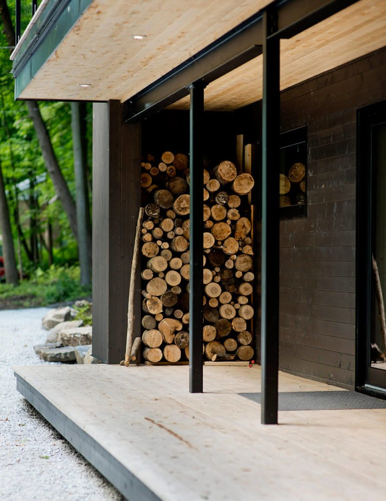 Here's a closer view, highlighting the abundant firewood storage and dark stained exterior panels.