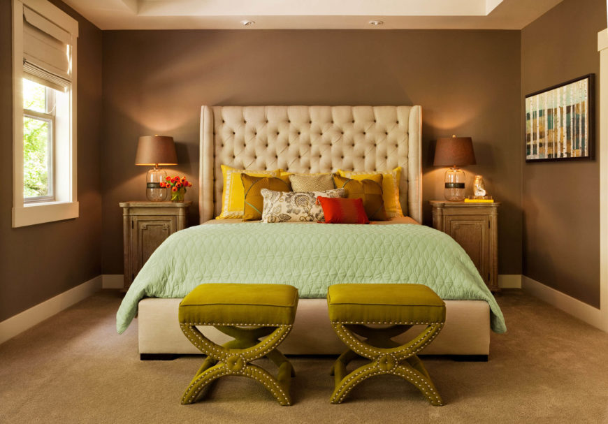 The primary bedroom comprises a unique variation on the home's color theme, with a vibrant beige button tufted headboard standing against mocha brown walls over dark beige carpet. A pair of rustic wood side tables flank the bed.